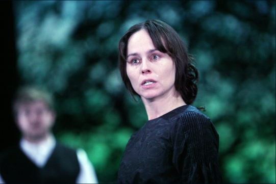 Tara Fitzgerald stands tearfully, dressed in black