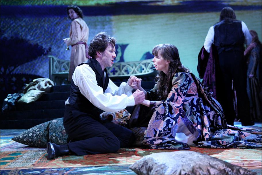 Jo Stone-Fewings as Leontes, in a white shirt and black waistcoat, kneeling and holdings hands with Hermione, played by Tara Fitzgerald, also kneeling and wearing a wide patterned robe