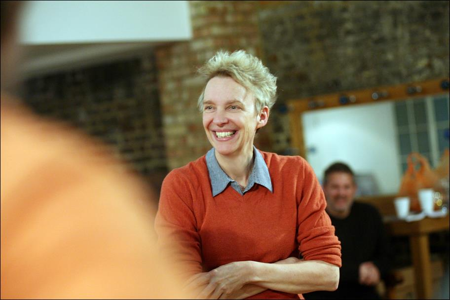 A woman in a red jumper with short blonde hair stands with her arms folded, smiling