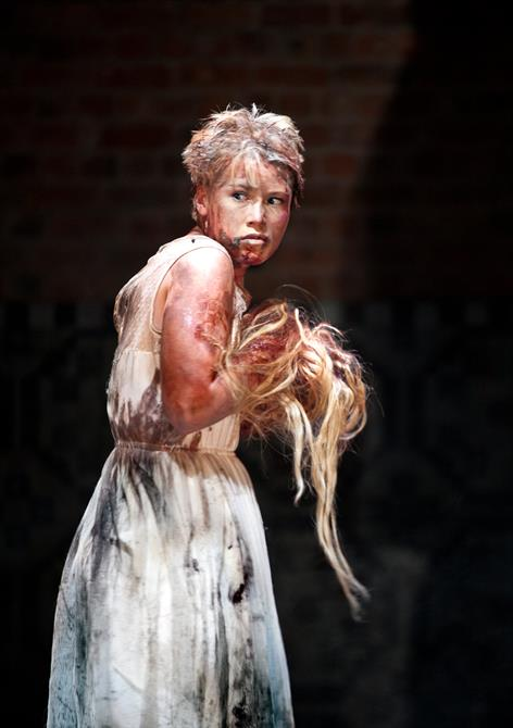 Production image of Rose Reynolds (Lavinia) clutching hair.