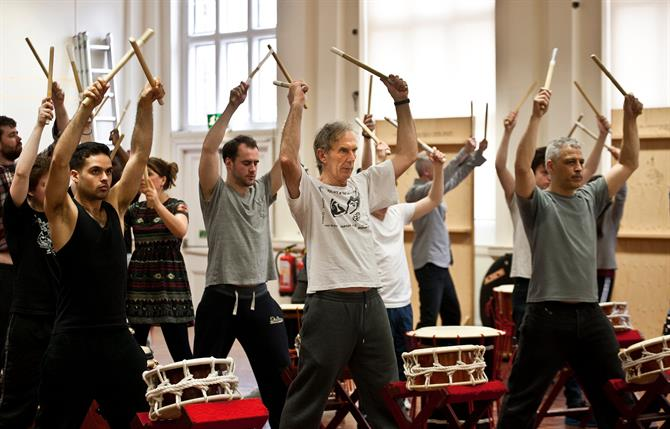 Rehearsal image of the cast of Titus Andronicus in a drumming workshop.