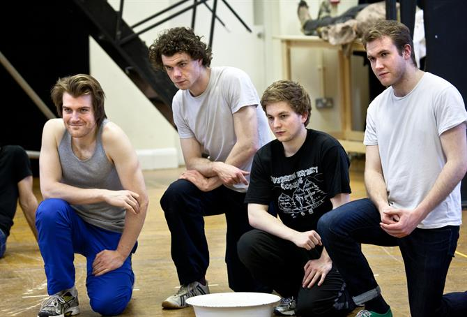 Rehearsal image of members of the Titus Andronicus cast crouching.