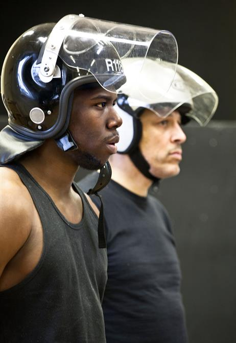 Rehearsal image of Dwane Walcott (left) and David Rubin (right)wearing riot helmets.