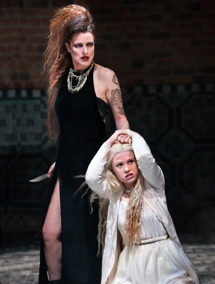 Katy Stephens as Tamora, in a black velvet dress, holding a knife in her right hand and Lavinia (Rose Reynolds) by the hair in her left