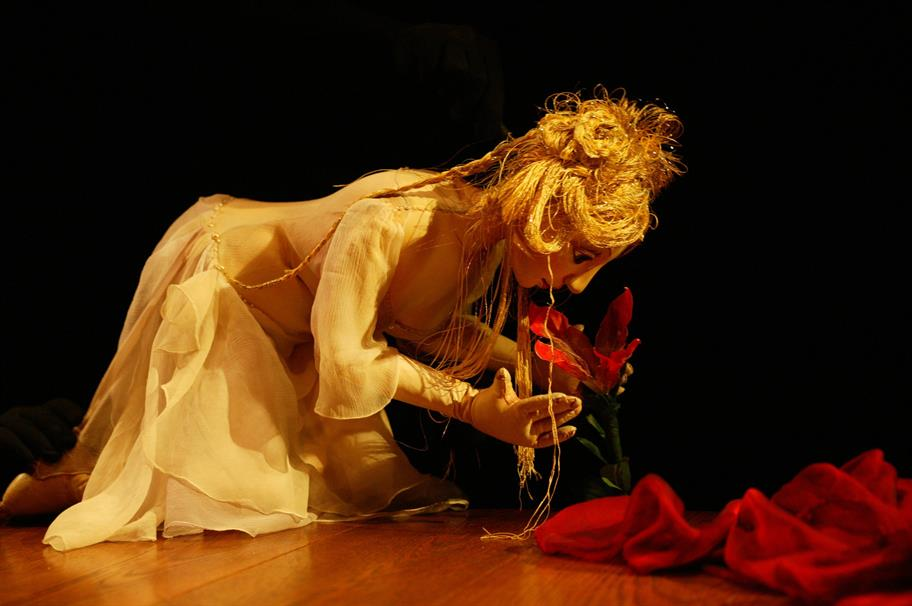 Venus puppet kneeling on the ground smelling a red flower