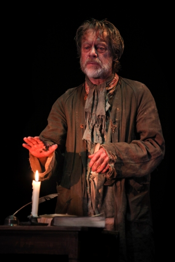 Stephen Boxer as William Tyndale holding his hand over a burning candle flame