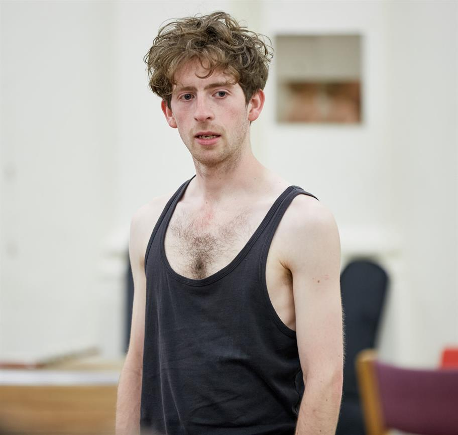 A young man with curly hair in a black vest