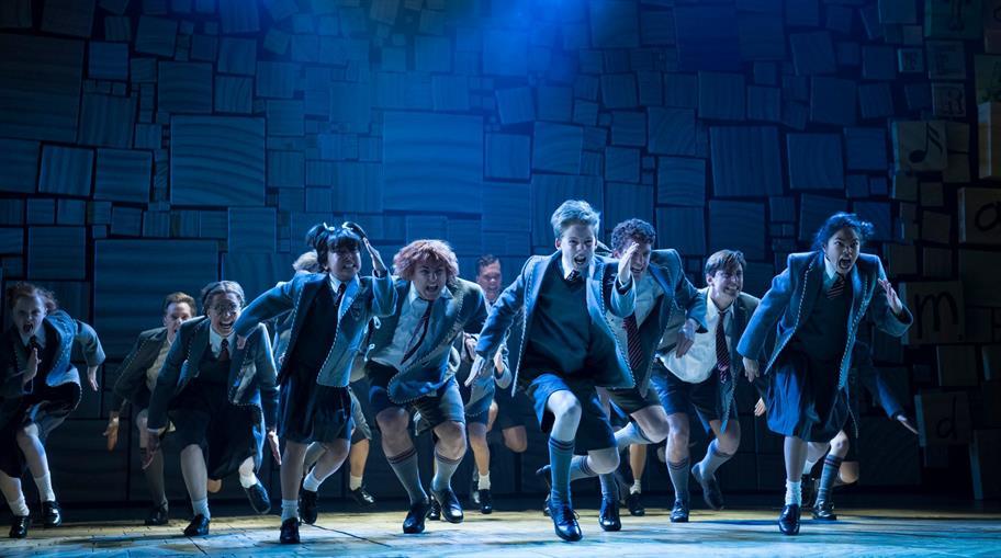 school children in uniform in a high-energy dance under blue lighting, on stage