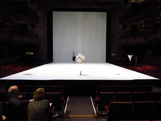 A view of the stage covered in white, with a white box and black bag suspended from lines above it
