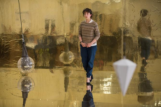 A woman stands on a shimmering golden floor in front of a golden wall