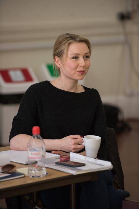 Director Polly Findlay in rehearsals, sitting at a table with a mug in her hand