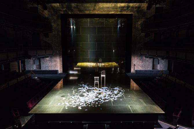 A shot of the stage with high wooden stools and bits of paper littered over it