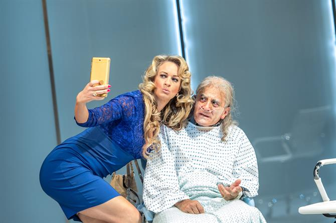 Annette McLaughlin as Lady Politic Would-Be posing for a selfie with Henry Goodman as Volpone.
