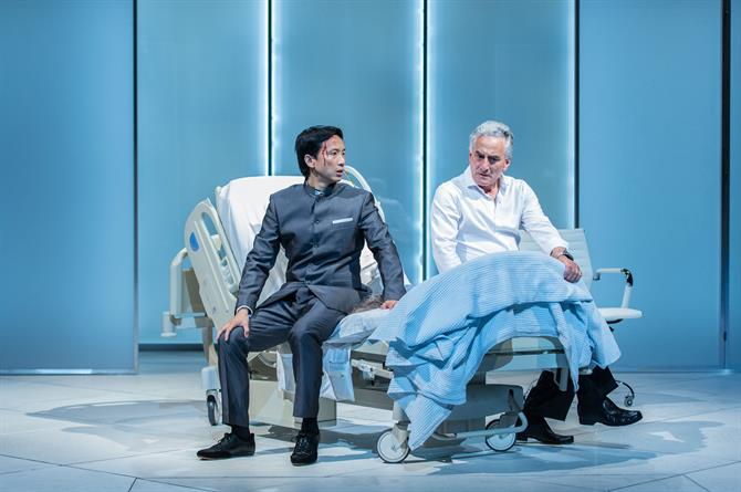 Orion Lee as Mosca and Henry Goodman as Volpone both seated on the hospital style bed.