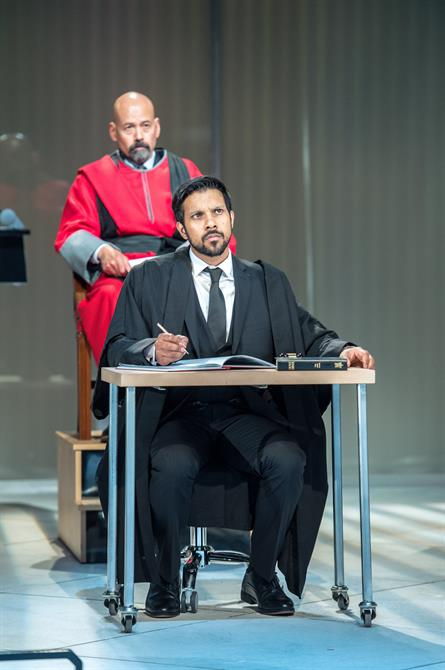A man in a red robe sits behind a man in black suit and robes at a desk.