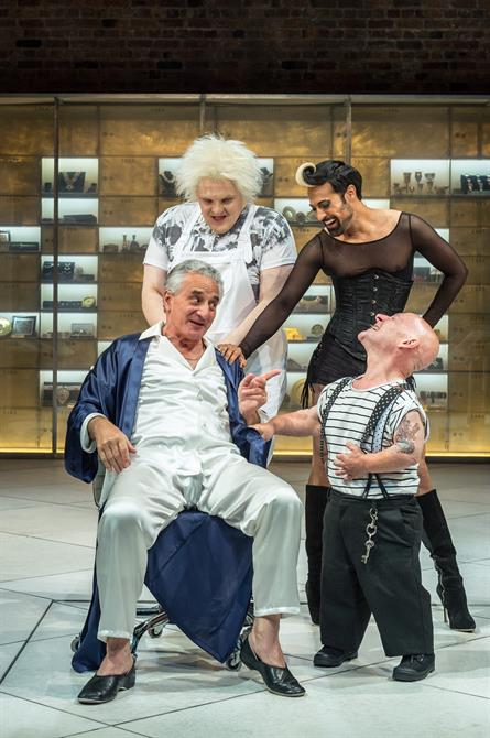 Production image of a seated Henry Goodman as Volpone surrounded by his performers Julian Hoult as Castrone, Ankur Bahl as Androgyno and Jon Key as Nano.