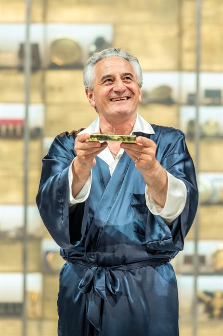Production image of Henry Goodman as Volpone holding a gold bar.