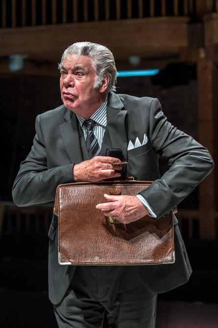 Matthew Kelly as Corvino clutching a brown business bag.