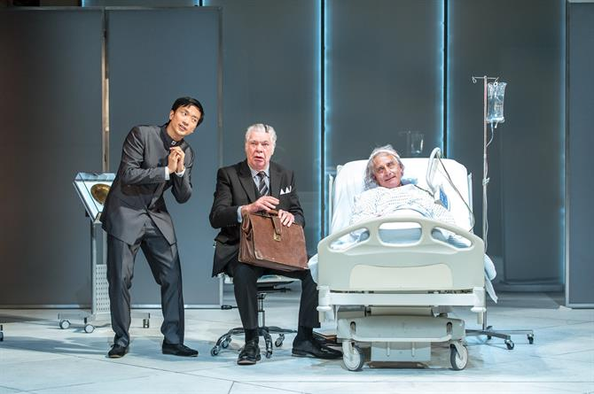 Two men in suits next to a man lying in a hospital bed.