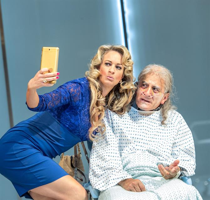 Annette McLaughlin as Lady Politic Would-Be, wearing a blue dress and bending over Henry Goodman's Volpone, who is in a hospital gown, to take a selfie