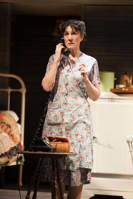 Harriet Walter stands on stage with a telephone