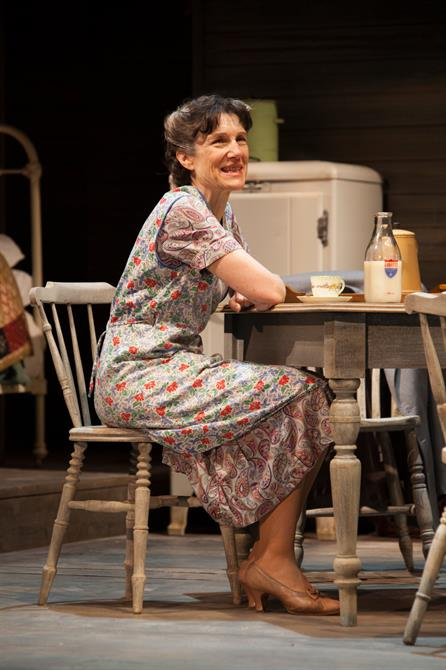 Harriet Walter on stage sitting at the dining table