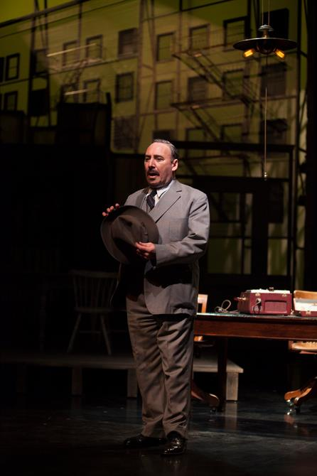 Antony Sher stands on stage wearing a suit and holding his hat on stage