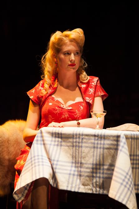 A woman sits at a table she is dressed in a red dress