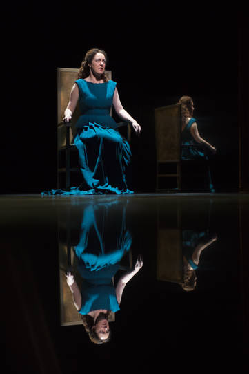 Derbhle Crotty as Hecuba, seated on her throne which is reflected in the floor