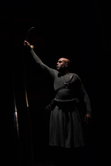 Chu Omambala as Odysseus in Hecuba. His right arm outstretched