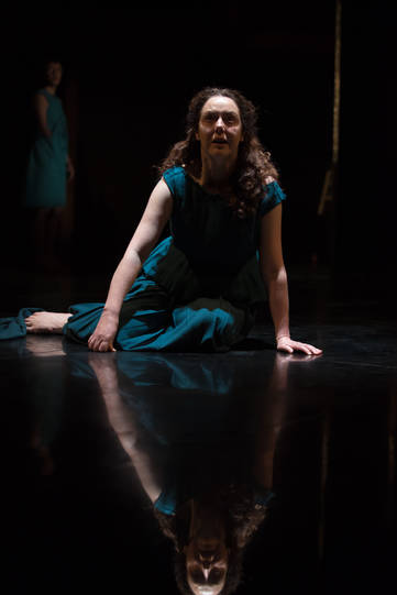 Derbhle Crotty as Hecuba seated on the floor