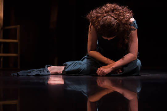 Derbhle Crotty as Hecuba seated on the floor, head bowed