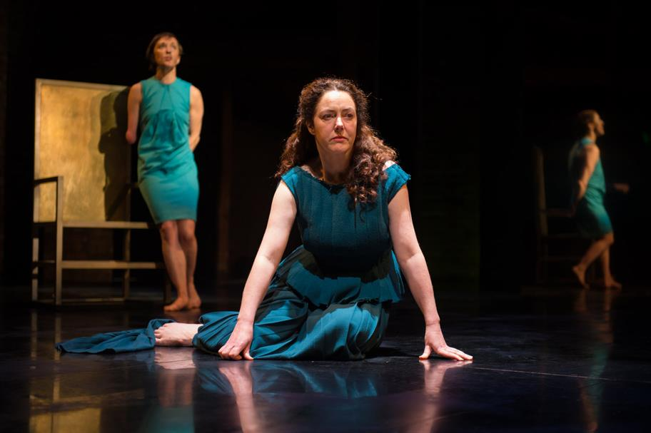 Derbhle Crotty as Hecuba in a blue dress kneels on the floor while Nadia Albina as Cassandra behind her leans on the throne