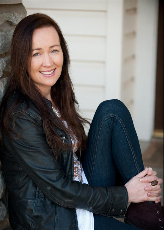 Marina Carr seated on the floor with her left leg drawn up to her chest, wearing a black leather jacket