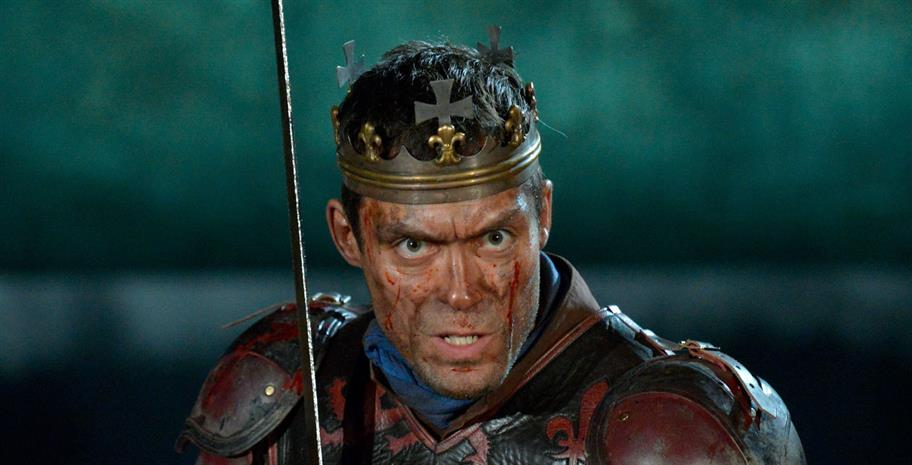 Alex Hassell as Henry V, wearing a crown and armour and holding a sword