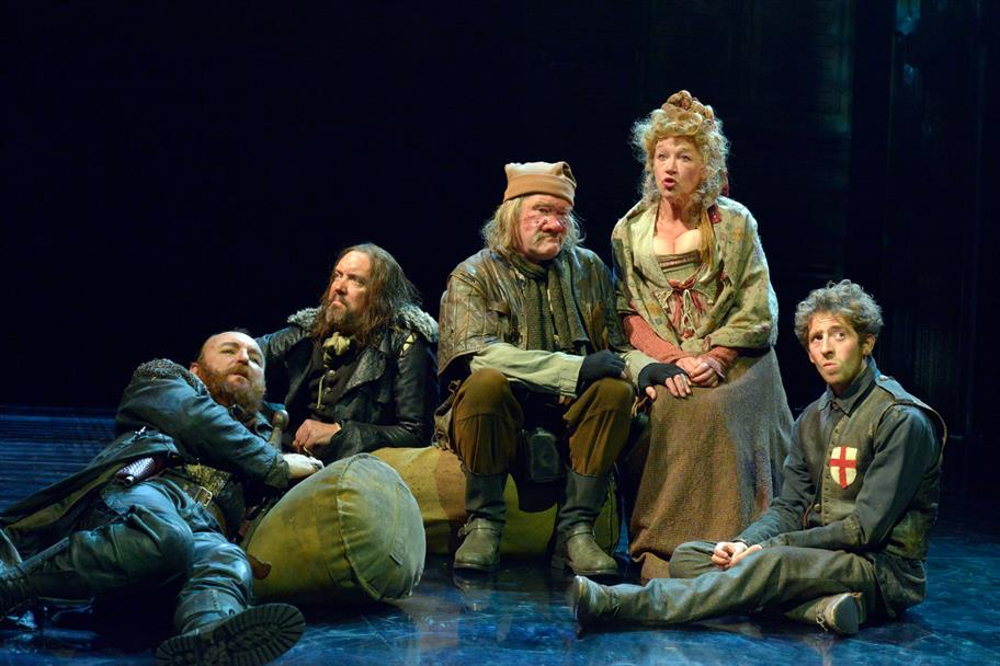 The company of Henry V sitting on the floor in period costumes