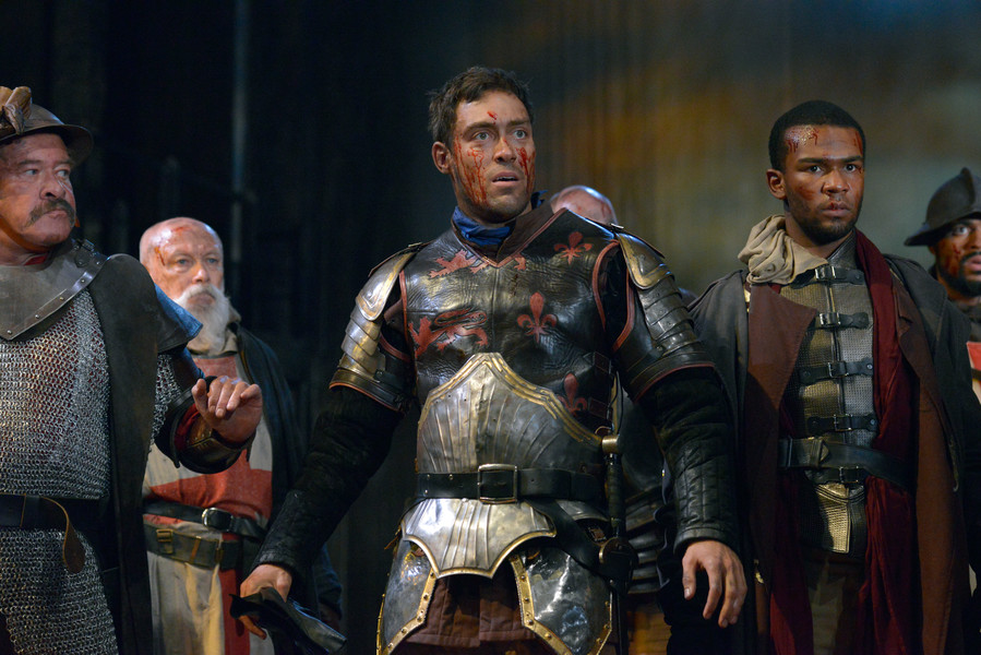 Alex Hassell as Henry V, with blood on his face and wearing leather and metal armour, standing with other soldiers
