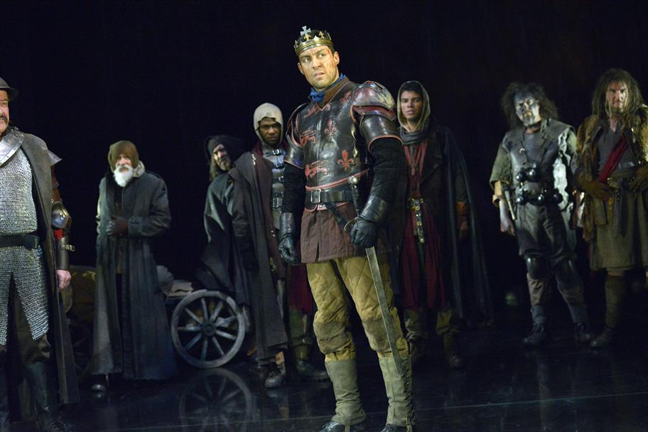 Alex Hassell as Henry V, in battle armour, wearing a crown and standing with other soldiers in various costumes