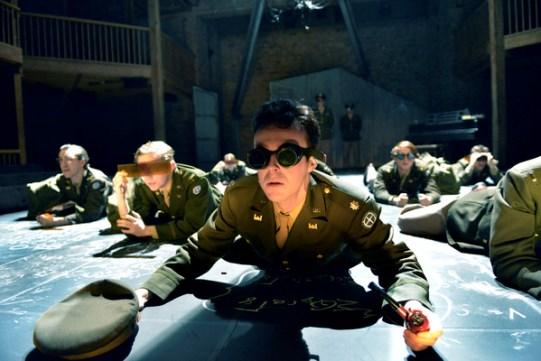 John Heffernan in Oppenheimer, lying on the floor with goggles on.