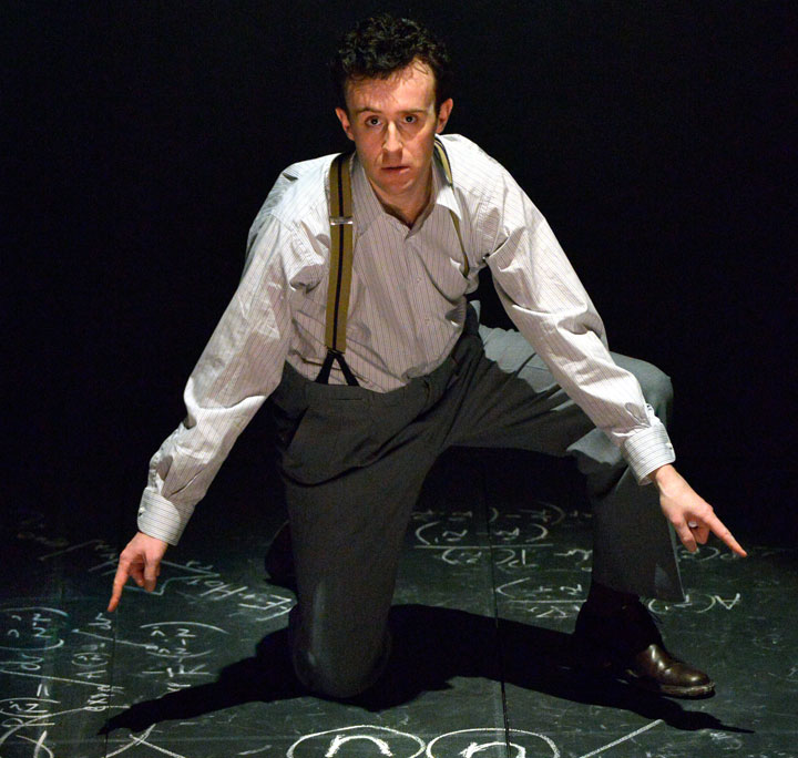 Oppenheimer, played by John Heffernan crouching down on floor scribbled with chalk