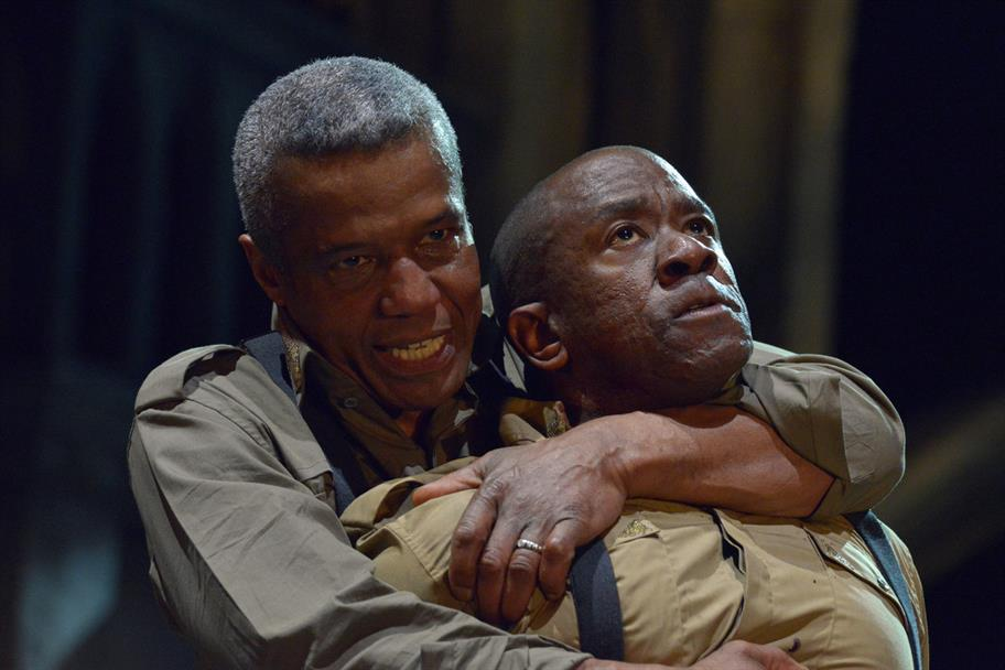Othello (Hugh Quarshie) holding Iago (Lucian Msamati) tightly by the neck, both men wearing grey-ish military shirts