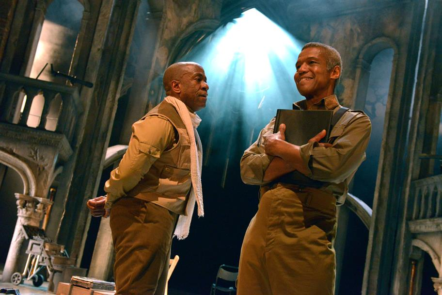 Lucian Msamati as Iago, wearing a white scarf, talking to Othello, played by Hugh Quarshie