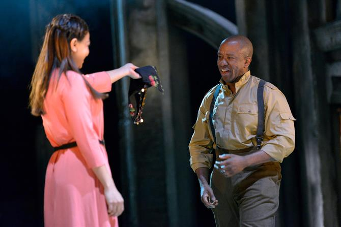 Ayesha Dharker as Emilia, wearing a pink dress and holding out a black handkerchief to Lucian Msamati as Iago
