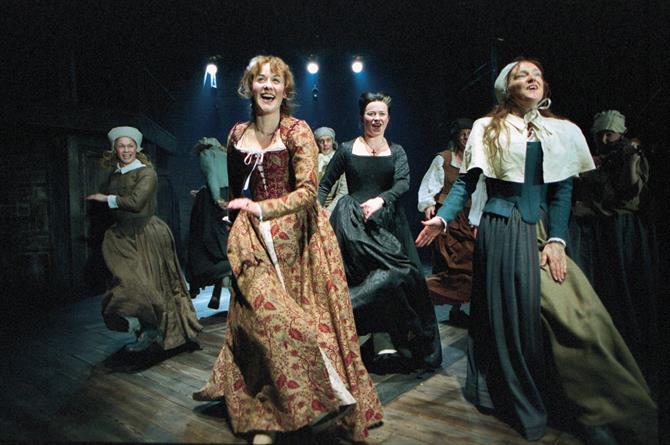 An image from the Tamer Tamed at the Swan Theatre showing Alexandra Gilbreath leading a dance in a patterned red dress in front of seven other actresses