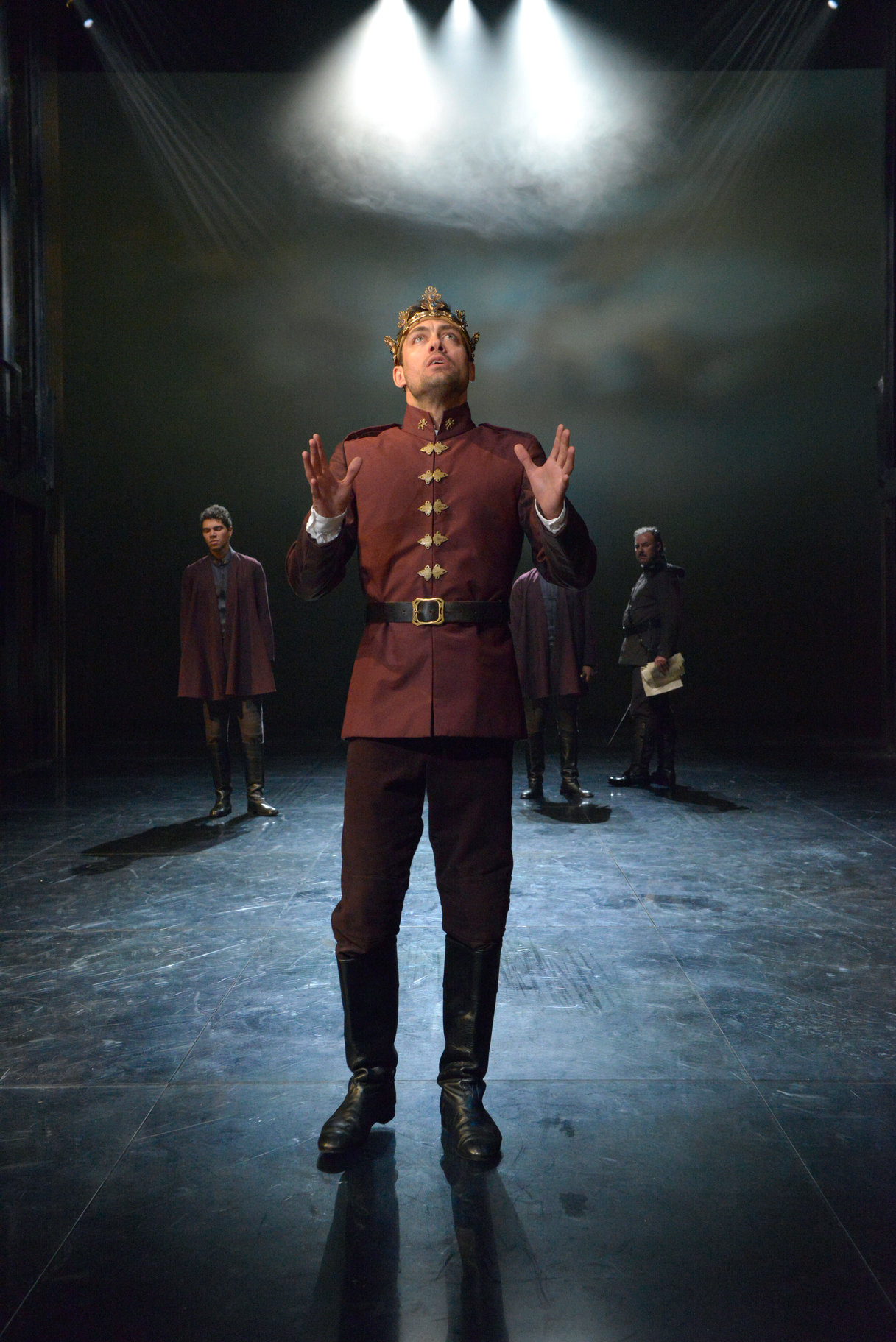 Henry V stands wearing his crown and raising his hands in the 2015 production of Henry V