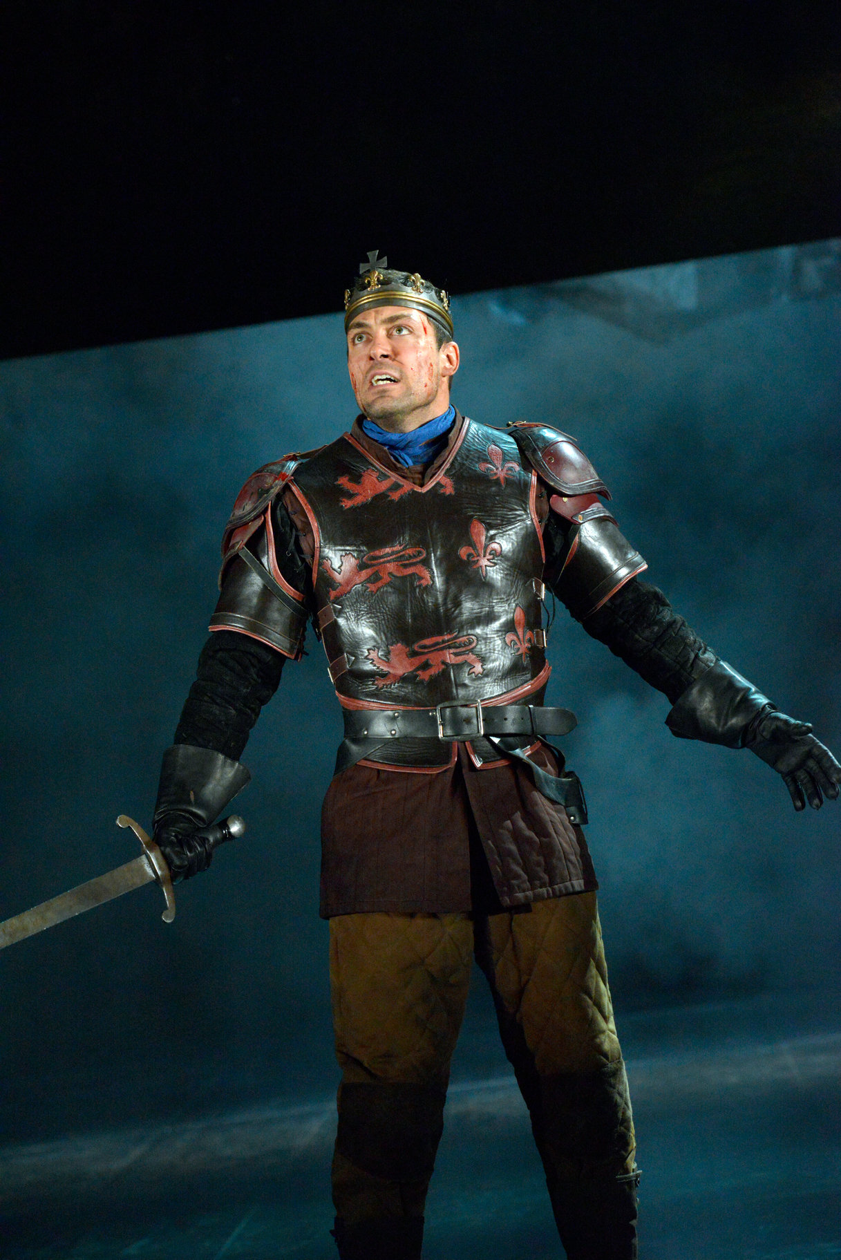 Henry stands on stage alone, in armour with his sword outstretched as he rallies his men in the 2015 production of Henry V