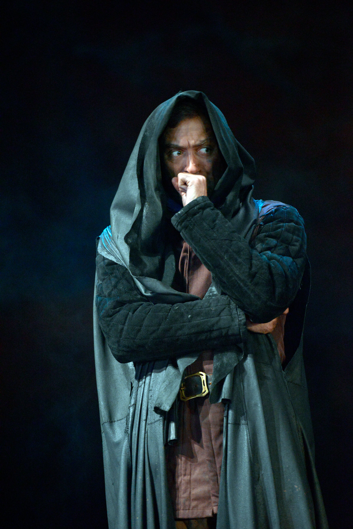 Henry in disguise wearing a dark cloak over his clothes and the hood pulled up over his head in the 2015 production of Henry V