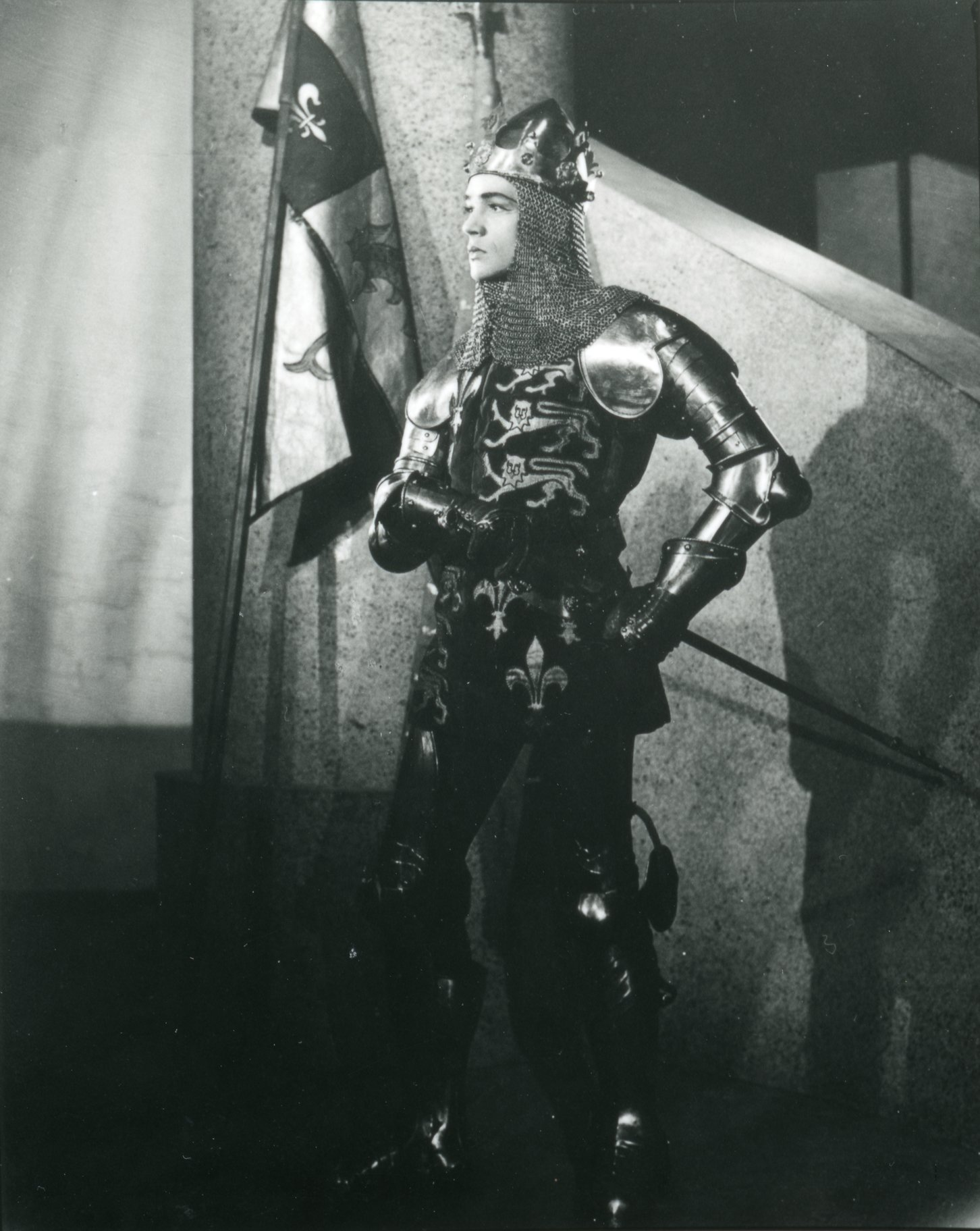 Paul Scofield stands wearing chain mail armour and crown as Henry V in the 1946 production of Henry V