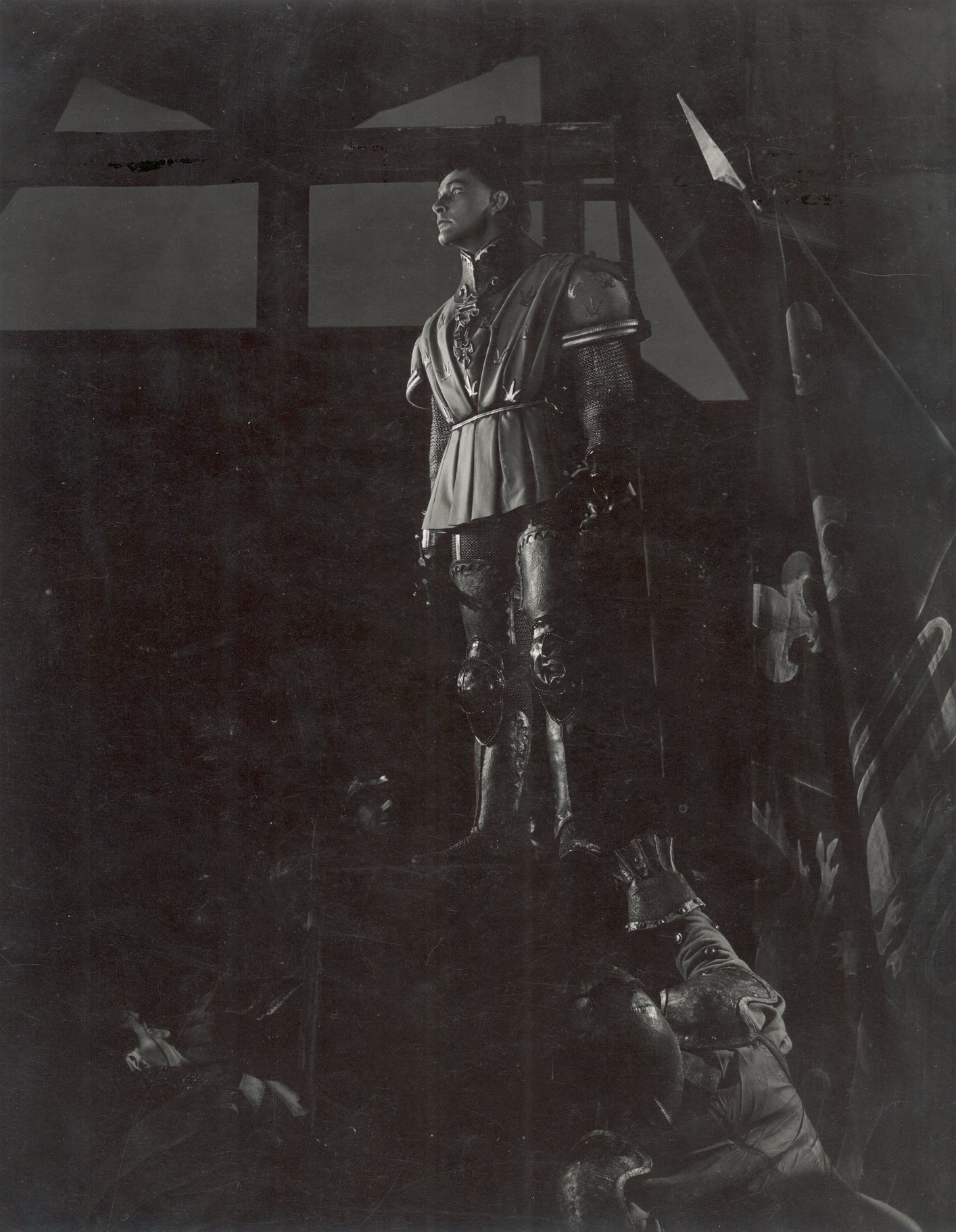 Henry stands on a ladder, looking down at some soldiers and urges the troops in the 1951 production of Henry V