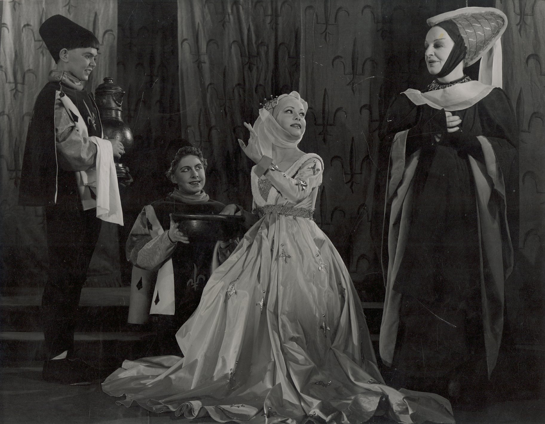 Katherine sits down, dressed in white silk, as her maid Alice stands beside her and they practice English, in the 1951 production of Henry V